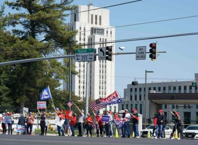 Supporters of Donald Trump hold signs and wave flags outside Walter Reed medical center in Bethesda, Maryland, on 4 October.