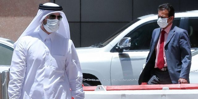 Men wearing protective masks walk by in Qatar's capital Doha, on May 17, 2020, as the country begins enforcing the world's toughest penalties for failing to wear masks in public, as it battles one of the world's highest coronavirus infection rates. - More than 30,000 people have tested positive for COVID-19 in the tiny Gulf country, 1.1 percent of the 2.75 million population, although just 15 people have died. Violators of the new rules will face up to three years in jail and fines of as much as $55,000. (Photo by KARIM JAAFAR / AFP) (Photo by KARIM JAAFAR/AFP via Getty Images)