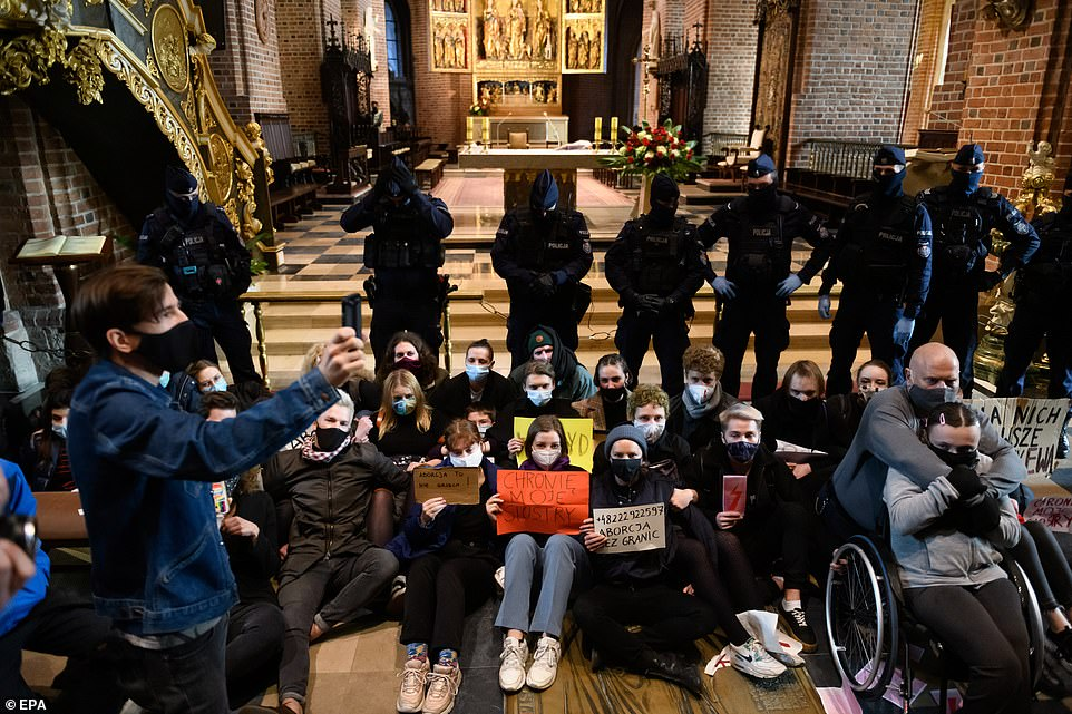 Protesters targeted Catholic churches across Poland on Sunday in the fourth straight day of upheaval against a near-total ban on abortion in the Catholic EU country. Pictured: People take part in a protest at the Archcathedral Basilica of St. Peter and St. Paul in Poznan