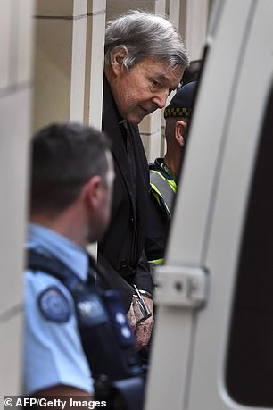 Cardinal George Pell is escorted in handcuffs from the Supreme Court of Victoria in Melbourne on August 21, 2019