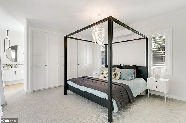 Eye-catching:The black-framed bed and beaded chandelier hanging from the roof match photos on the Airbnb listing (above)