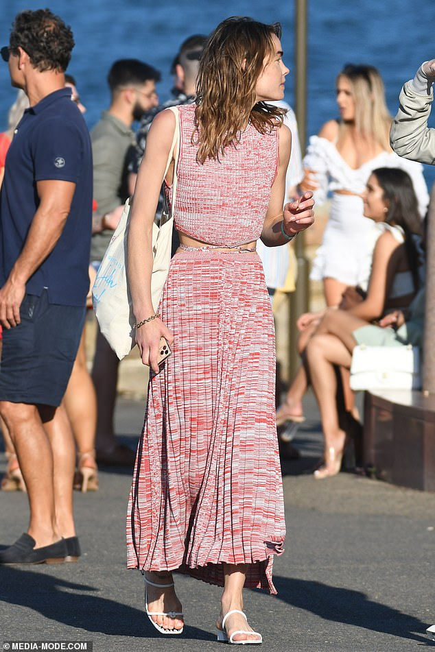 Glamourous: She carried her belongings in a canvas tote bag, and completed her look with a pair of white heeled sandals, gold hoop earrings and a matching bangle