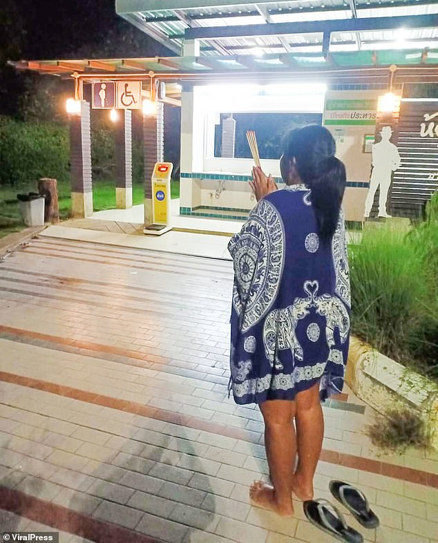 His girlfriend, Nanthakan Kaewsiri, 43, told police he had run away when they stopped at a service station (Kaewsiri pictured praying at the station) on Tuesday afternoon after returning from a holiday together