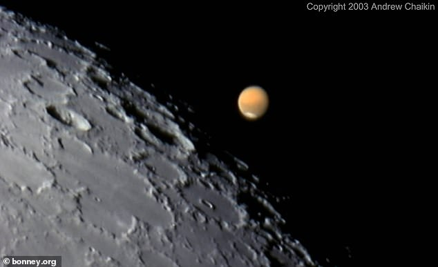 The conjunction starts at 11:35pm ET on Friday, October 2, with the closest approach seen shortly after midnight. Pictured is the event captured in 2003. A powerful telescope was able to snap an image of the moon's surface with Mars hanging close by