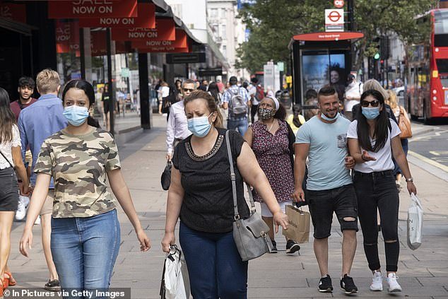 Public Health England last night admitted nearly 16,000 cases had been missed in the space of a week – most of them in the past few days. Pictured: People in face masks on the street of London