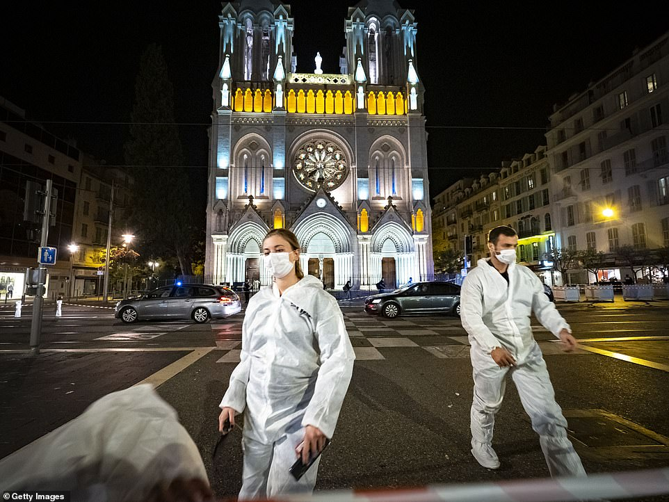 Forensic officers work at night in front of Notre Dame Basilica in Nice after a terror attack on a Catholic church