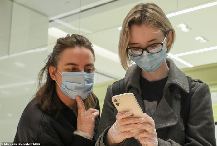 People examine a new smartphone at a re:Store shop in Petrovka Street with personal protective equipment on including masks and gloves