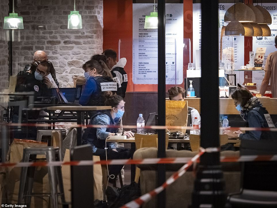 Forensic officers work at night in a coffee shop near Notre Dame Basilica in Nice following an Islamist terror attack