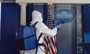 A member of the cleaning staff sprays the James Brady Briefing Room.