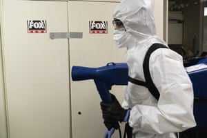 A member of the cleaning staff sprays press areas of the White House.