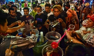 Protesters get drinks for themselves from a street food vendor's stall during an anti-government rally in Bangkok.