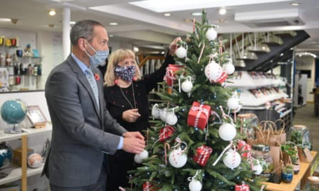 William Coe, owner of Coes department store, decorating a Christmas tree with a colleague.