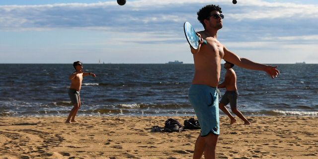 A group of men play sports on the St Kilda beach in Melbourne, Australia, Wednesday, Oct. 28, 2020. Melbourne, Australia's former coronavirus hotspot, emerged from a lockdown at midnight Tuesday, restaurants, cafes and bars were allowed to open and outdoor contact sports can resume. (AP Photo/Asanka Brendon Ratnayake)