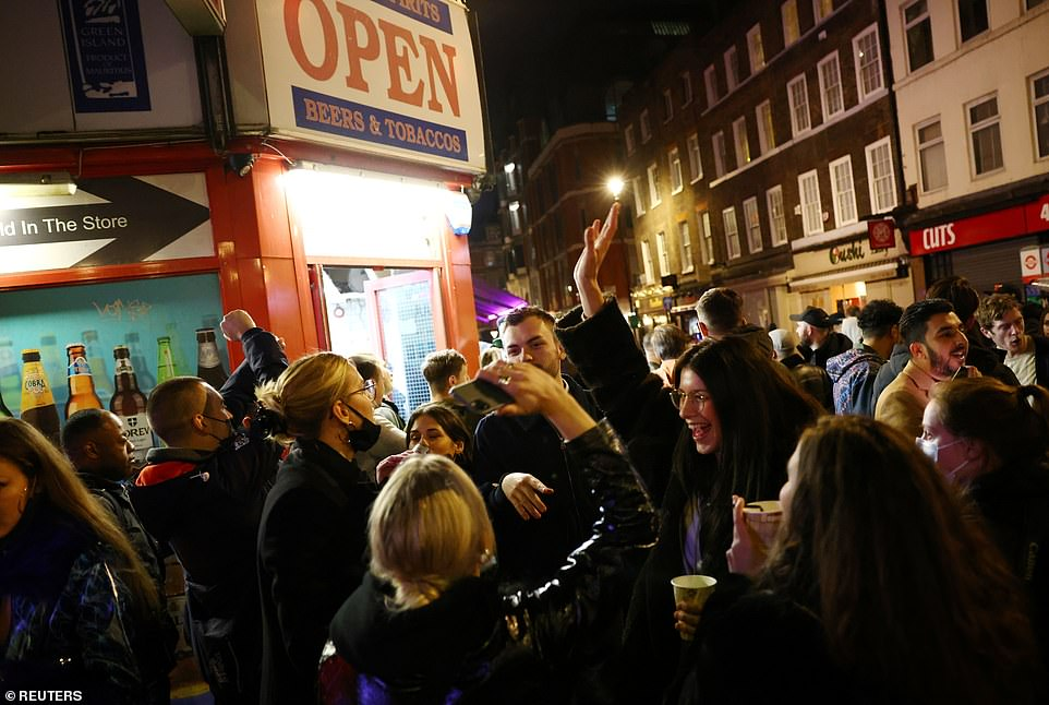 People are seen enjoying drinks in the street as pubs close ahead of the lockdown in Soho in London. Social distancing measures appeared to be ignored