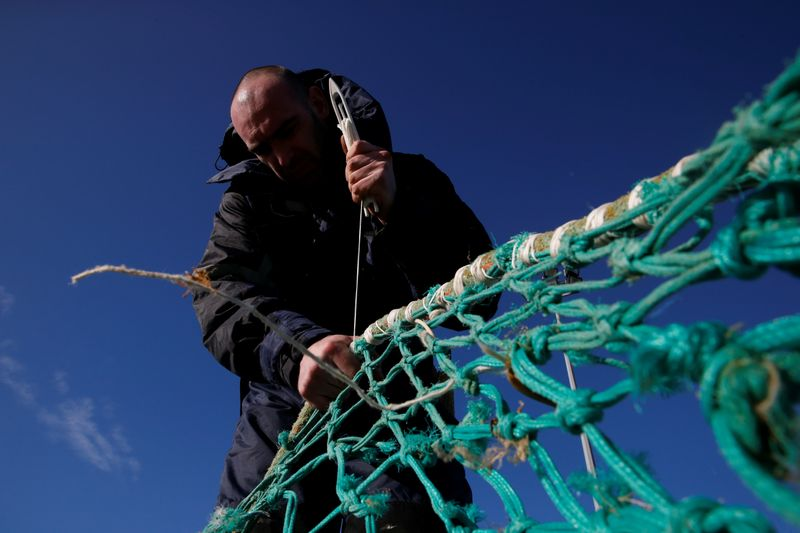 © Reuters. A fisherman repairs a fishing net on the dock of the port in Boulogne-sur-Mer