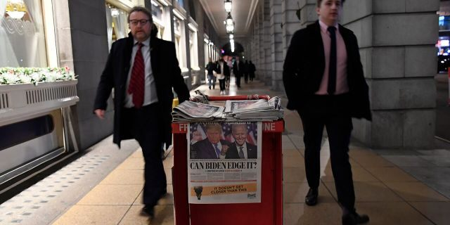 People walk past a pile of Evening Standard newspapers displaying a picture of US presidential candidates President Donald Trump and Joe Biden, in London, Wednesday, Nov. 4, 2020. (AP Photo/Alberto Pezzali)