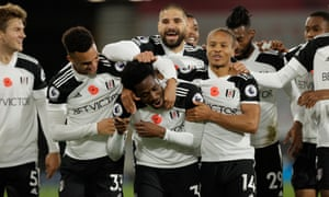 Ola Aina (centre) is mobbed by his Fulham teammates.