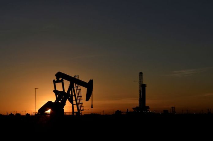 © Reuters. FILE PHOTO: A pump jack operates in front of a drilling rig at sunset in an oil field in Midland