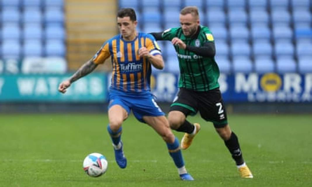 Oliver Norburn carries the ball away from Ryan McLaughlin during Shrewsbury's game against Rochdale in October.