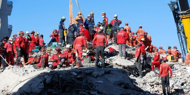 Members of rescue services search in the debris of a collapsed building for survivors in Izmir, Turkey, early Sunday, Nov. 1, 2020.