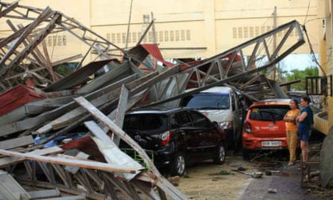 People stand next to cars damaged after a gymnasium collapsed in Tabaco, Albay province