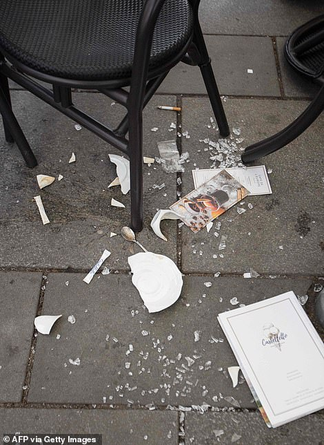A broken plate lies on the ground next to chairs and tables of a cafe near Stephansplatz in Vienna on Tuesday monring