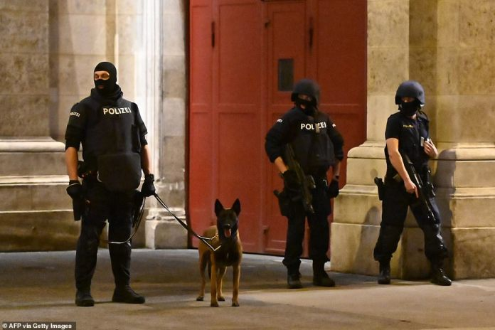 Armed policemen stand witha a dog near the State Opera in the center of Vienna this evening while the manhunt continues