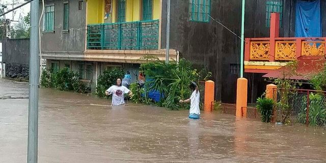 Residents walk along floodwaters in Daraga, Albay province, central Philippines as Typhoon Goni hit the area Sunday, Nov. 1, 2020.