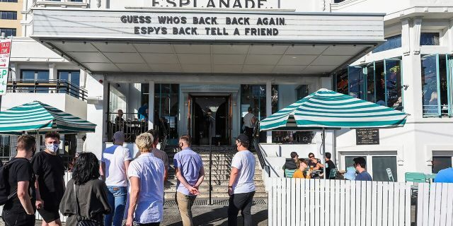 People line up outside a popular pub and restaurant in St Kilda in Melbourne, Australia, Wednesday, Oct. 28, 2020. Melbourne, Australia's former coronavirus hotspot, emerged from a lockdown at midnight Tuesday, restaurants, cafes and bars were allowed to open and outdoor contact sports can resume. (AP Photo/Asanka Brendon Ratnayake)