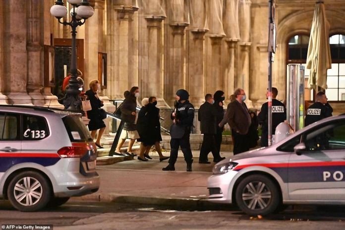 Opera guests leave the state opera under the supervision of armed policemen, in the center of Vienna after the shootings
