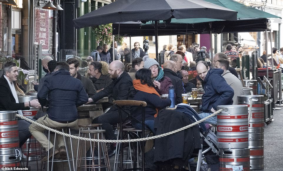 The shutters will come down on pubs, restaurants and non-essential stores by the end of the day, signalling the start of yet more swingeing restrictions. Pictured, drinkers in Borough Market