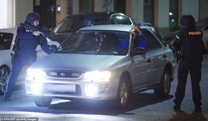 Armed policemen control persons inside a car near the Schwedenplatz in the center of Vienna following the shootings this evening