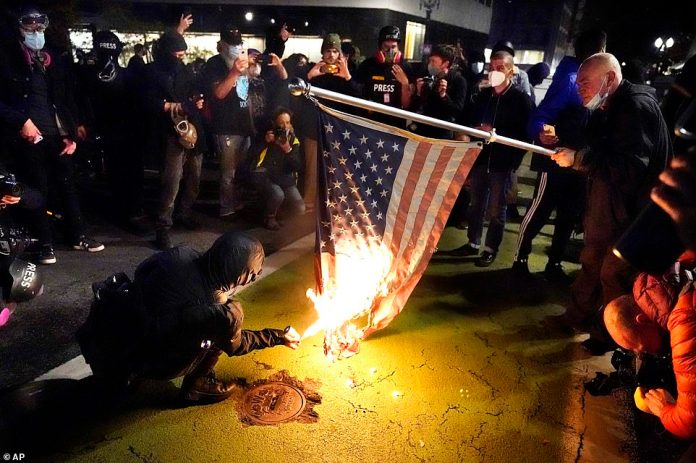 SEATTLE: A protester lights an American flag on fire during a demonstration in Seattle on Wednesday