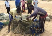 Fishermen mending their fishing net