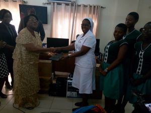 Dr Mrs Sylvia Boye making a symbolic presentation to some of the headmistresses of the beneficiary schools.