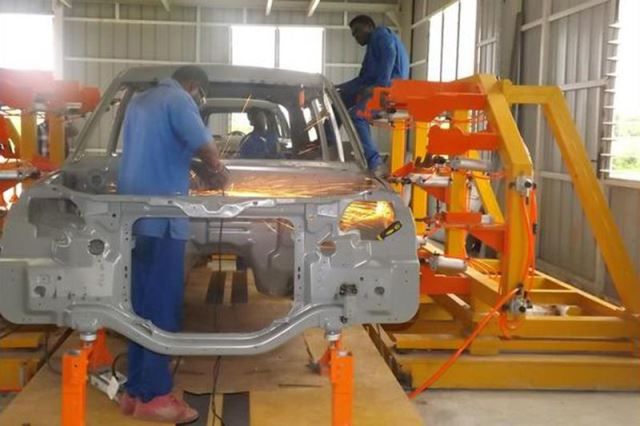 This shows the state of Kantanka's factory, where we see a complicated stamping that I can not believe was produced in Ghana itself. I also can not explain why the worker is taking a grinder to the firewall. Photo via Africarm.org