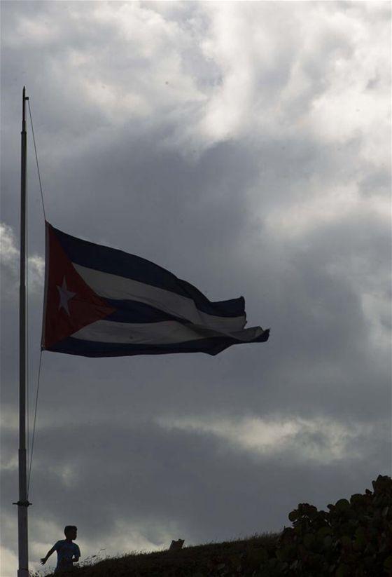 A boy stands below a Cuban national flag at half-mast in honor of Cuban revolutionary leader Fidel Castro, in Havana, capital of Cuba, on Nov. 27, 2016. [Photo/Xinhua]
