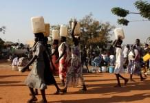 FILE (Xinhua) -- South Sudanese women carry water in a UN camp in Juba, capital of South Sudan, Dec. 22, 2013.