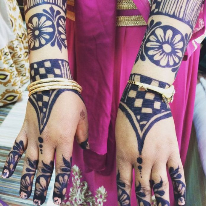 Sally's arms and hands have been decorated in advance with henna