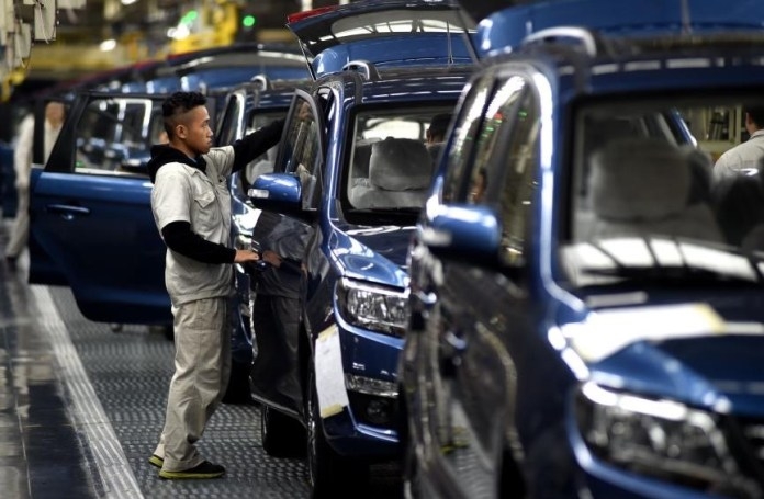 Workers conduct a final check on vehicles before they go off the production line at an assembly workshop of a passenger vehicle manufacturing base of Dongfeng Liuzhou Motor Co., Ltd., a subsidiary of Dongfeng Motor Group, Jan. 2018. (Photo from CFP)