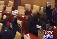 """Some NDC MP's holding placards with the inscription """"BLOODY WIDOW"""" as they walk of out parliament"""