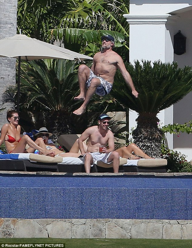 Having fun: Her husband Eric took a chance to do some bombing into to the pool