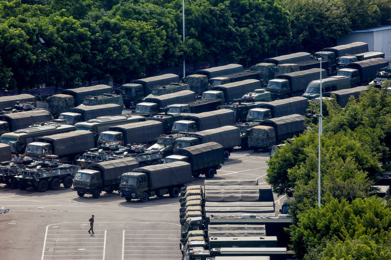 © Reuters. Servicemen walk past military vehicles in the parking area of the Shenzhen Bay Sports Center in Shenzhen across the bay from Hong Kong