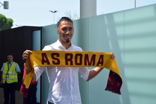 Chris Smalling holds a Roma scarf after completing a move from Manchester United