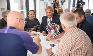 Gary Mabbutt looking through football memorabilia at a workshop for people from Tottenham living with dementia.