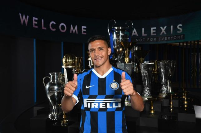 Alexis Sanchez poses in front of Inter Milan's trophy cabinet