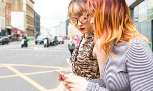 women looking at a phone in the street