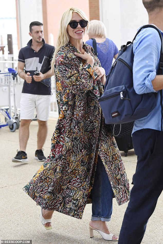 Glamorous: The actress wrapped up in a rich floral tapestry mac as she sauntered out of her hotel in slip-on heels