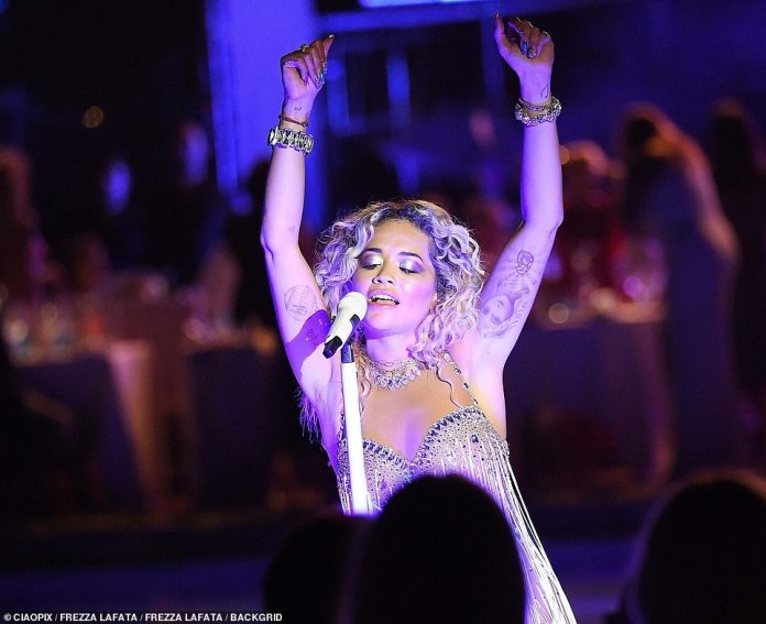 Putting on a show: Rita Ora put on an animated display as she hit the stage in a bejewelled silver leotard in Porto Cervo, Italy, on Monday