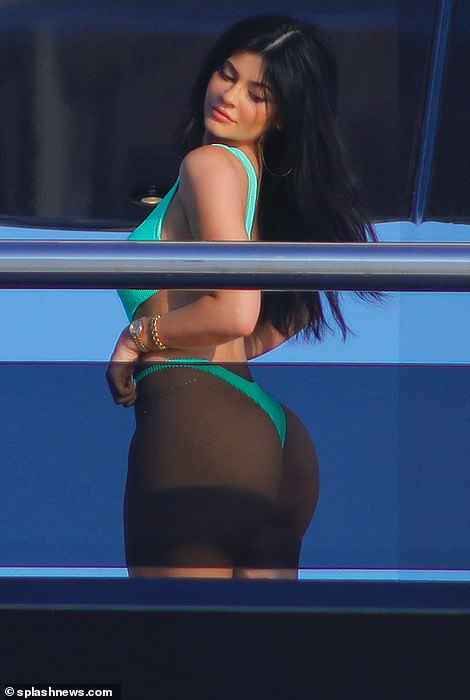 Peachy:The billionaire, 22, looked sensational as she displayed her very ample assets and peachy posterior in a tiny turquoise thong swimsuit